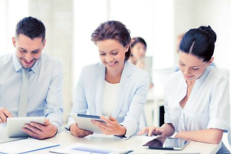 common goals: smiling business team working with tablet pcs in office