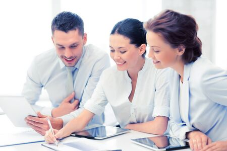 pcs: friendly business team with tablet pcs having discussion in office Stock Photo
