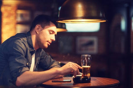bad habit: people and bad habits concept - man drinking beer and smoking and shaking off ashes of cigarette at bar or pub