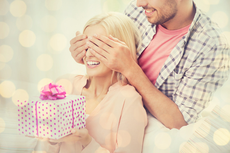 gift giving: relationships, love, people, birthday and holidays concept - happy man covering woman eyes and giving gift box over lights background