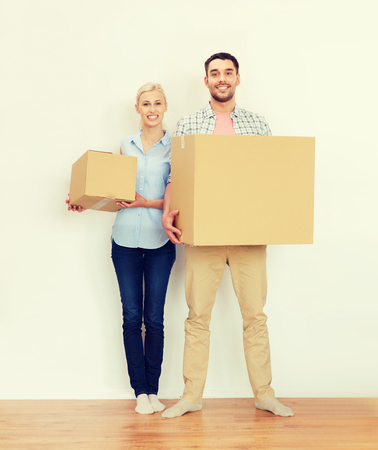 home, people, repair and real estate concept - happy couple holding cardboard boxes and moving to new place Stock Photo