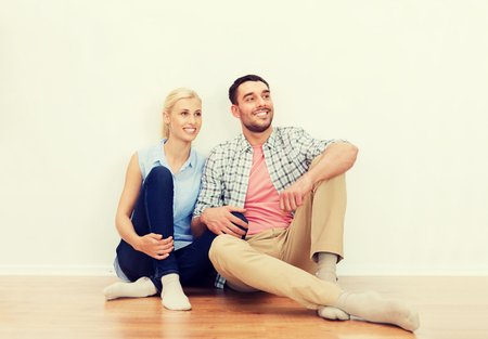 home, people, repair, moving and real estate concept - happy couple of man and woman sitting on floor at new place