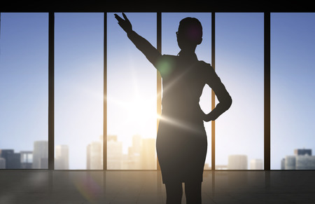 business direction: business and people concept - silhouette of woman pointing hand and showing direction over office window background Stock Photo