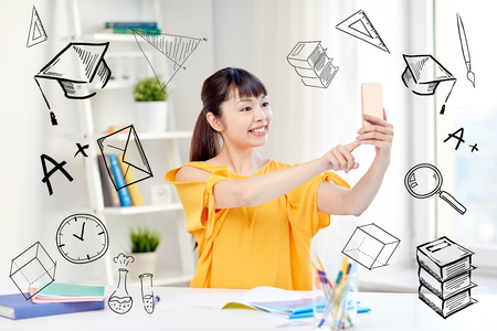 young asian: people, education, high school and learning concept - happy asian young woman student taking selfie with smartphone at home with doodles Stock Photo