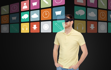 mediated: 3d technology, virtual reality, multimedia, entertainment and people concept - happy young man in virtual reality headset or 3d glasses witj computer icons over black background