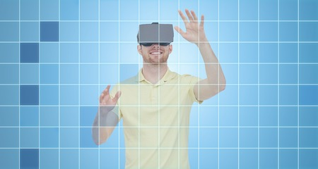 entertainment background: 3d technology, virtual reality, entertainment and people concept - happy young man with virtual reality headset or 3d glasses playing game over blue grid background