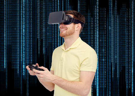 mediated: 3d technology, virtual reality, entertainment and people concept - happy young man with virtual reality headset or 3d glasses playing with game controller gamepad over binary code background