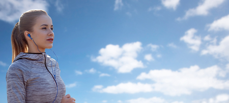 personas escuchando: fitness, deporte, la gente, la tecnología y el concepto de estilo de vida - mujer feliz corriendo y escuchando música en los auriculares sobre el cielo azul y las nubes de fondo Foto de archivo