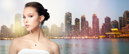 jewelry background: beauty, jewelry, wedding accessories, people and luxury concept - beautiful asian woman or bride with earring and pendant over evening dubai city lights and skyscrapers background