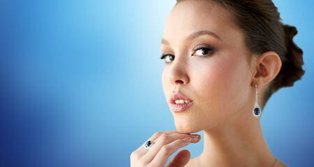 anillo de boda: belleza, joyas, accesorios de la boda, la gente y el concepto de lujo - cerca de la hermosa mujer asiática o la novia con el pendiente y el anillo de dedo sobre fondo azul