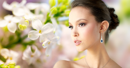 green gemstone: beauty, jewelry, wedding accessories, people and luxury concept - close up of beautiful asian woman or bride with earring over natural spring lilac blossom background