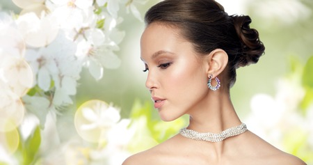 beauty, jewelry, accessories, people and luxury concept - close up of beautiful asian woman face with earring over natural spring cherry blossom background