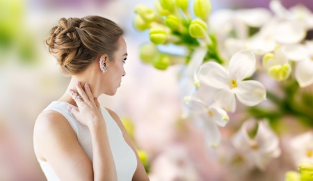 glamour luxury: glamour, beauty, jewelry and luxury concept - close up of beautiful woman with golden ring and diamond earring over natural spring lilac blossom background Stock Photo