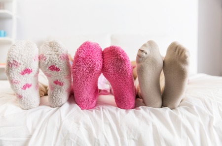 teen girls feet: friendship, people and pajama party concept - close up of women feet in socks on bed at home