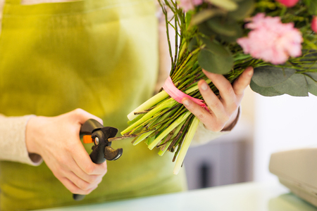 cropping: people, business, sale and floristry concept - close up of florist woman making bunch and cropping stems by pruner at flower shop