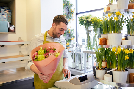 floristry: people, sale, retail, business and floristry concept - happy smiling florist man with bunch counting cost at flower shop cashbox