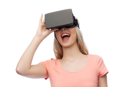 entertainment concept: technology, virtual reality, entertainment and people concept - happy young woman with virtual reality headset or 3d glasses Stock Photo