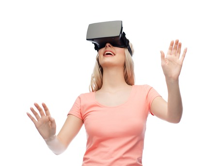 invisible: technology, virtual reality, entertainment and people concept - happy young woman with virtual reality headset or 3d glasses Stock Photo