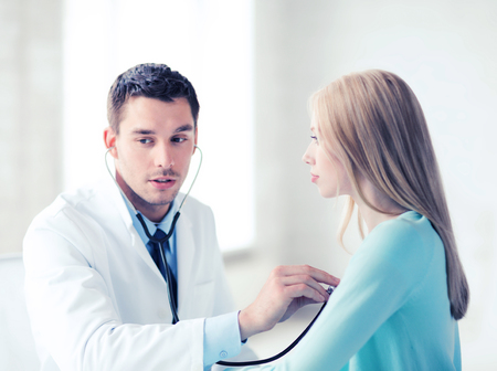 healthcare and medical - doctor with stethoscope listening to the patient in hospital Reklamní fotografie