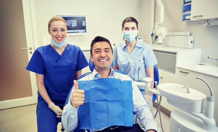 patient care: people, medicine, stomatology, gesture and health care concept - happy female dentist with assistant and man patient showing thumbs up at dental clinic office