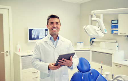 stomatologist: people, medicine, stomatology and healthcare concept - happy middle aged male dentist in white coat with tablet pc computer at dental clinic office Stock Photo
