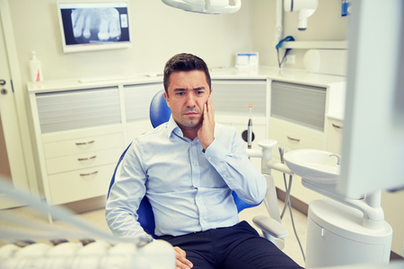 stomatological: people, medicine, stomatology and health care concept - unhappy male patient having toothache sitting on dental chair at clinic office Stock Photo