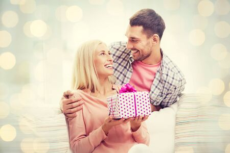 relationships, love, people, birthday and valentines day concept - happy man and woman with gift box at home over holidays lights background Stock Photo