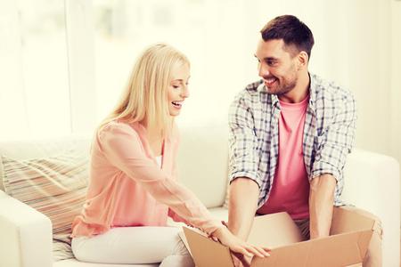 cajas de carton: la gente, la entrega, el transporte y el concepto de servicio postal - caja de cartón apertura feliz pareja o parcela en casa Foto de archivo