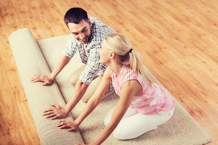 domesticity: people, repair and renovation concept - happy couple unrolling carpet or rug on floor at home