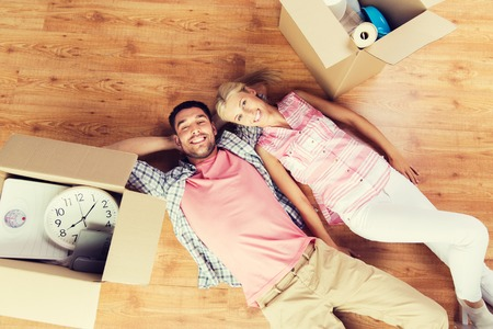 'young things': home, people, repair and real estate concept - happy couple with cardboard boxes and stuff lying on floor to new place Stock Photo