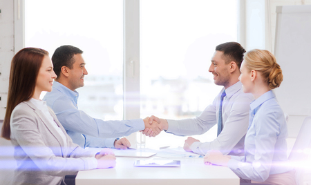 businessman in office: business and office concept - smiling business team having meeting in office