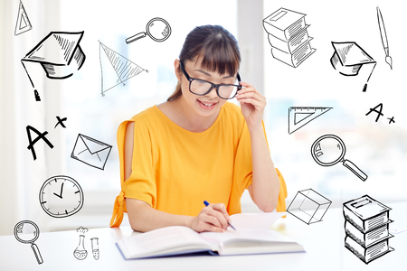 essay: people, education, high school and learning concept - happy asian young woman student with book and notepad writing at home over doodles