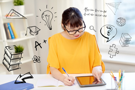 people, education, high school and learning concept - happy asian young woman student in glasses with tablet pc computer, book and notepad writing at home over doodles