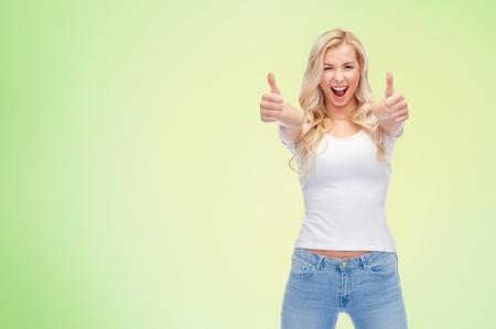 감정, 표현, 광고 및 사람들이 개념 - 행복 한 미소 젊은 여자 또는 녹색 자연 배경 위에 양손으로 엄지 손가락을 보여주는 흰색 t- 셔츠에 10 대 소녀가  스톡 콘텐츠