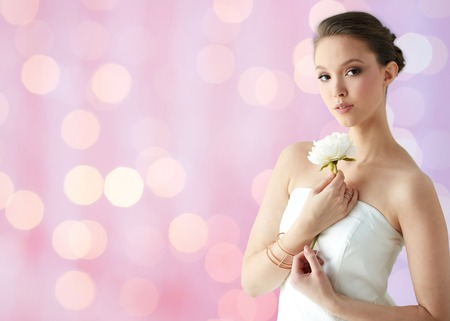 bride bangle: beauty, jewelry, people and luxury concept - beautiful asian woman or bride in white dress with peony flower, golden ring and bracelet over holidays lights background