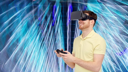 mediated: 3d technology, virtual reality, entertainment and people concept - happy young man with virtual reality headset or 3d glasses playing with game controller gamepad over spiral neon lights background Stock Photo