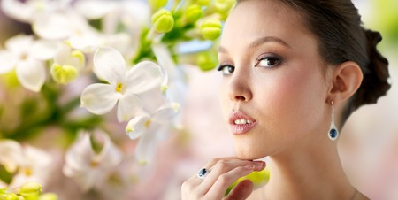 green gemstone: beauty, jewelry, wedding accessories, people and luxury concept - close up of beautiful asian woman or bride with earring and finger ring over natural spring lilac blossom background