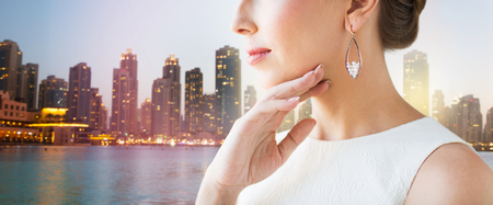 jewelry background: glamour, beauty, jewelry and luxury concept - close up of beautiful woman face with pearl earrings over singapore city skyscrapers background