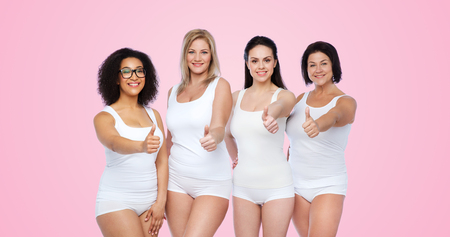 gesture, friendship, beauty, body positive and people concept - group of happy different women in white underwear showing thumbs up over pink background