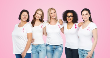black breast: diverse, healthcare and people concept - group of happy different size women in white t-shirts with pink breast cancer awareness ribbon over pink background