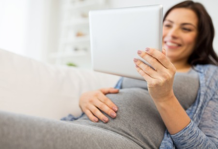 pregnancy, motherhood, technology, people and expectation concept - close up of happy pregnant woman with tablet pc computer at home
