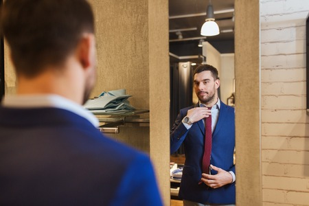 men in suit: sale, shopping, fashion, style and people concept - elegant young man choosing and trying jacket on and looking to mirror in mall or clothing store Stock Photo