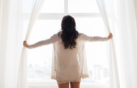people and morning concept - close up of happy woman opening window curtains at home Stock Photo