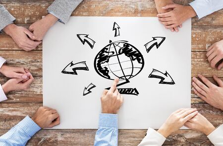 businesspeople: global business, people and team work concept - close up of creative team sitting at table and pointing finger to globe picture on paper in office Stock Photo