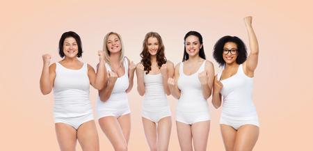 personas saludables: éxito, amistad, belleza, cuerpo positivo y concepto de la gente - grupo de mujeres felices del tamaño más en ropa interior blanca que celebran la victoria sobre el fondo de color beige