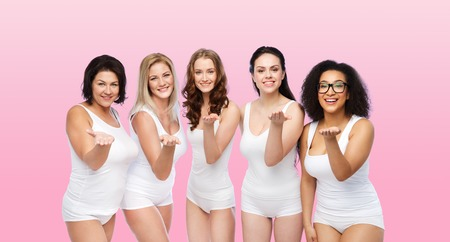 love blow: love, friendship, beauty, body positive and people concept - group of happy plus size women in white underwear sending blow kiss over pink background