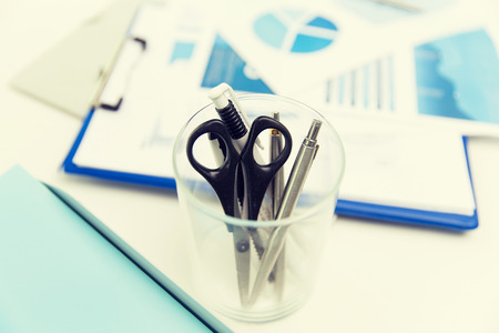 office supply: business, stationery and office supply concept - close up of organizer with scissors and pens over charts on table