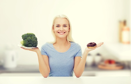 good food: healthy eating, junk food, diet and choice people concept - smiling woman choosing between broccoli and donut over kitchen background