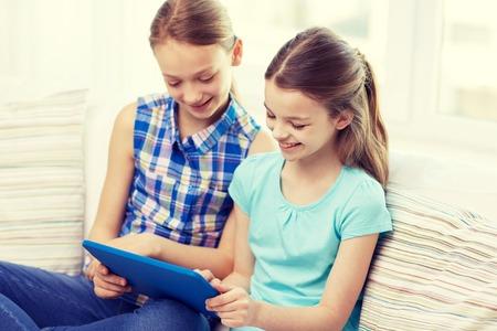 niños sentados: gente, niños, tecnología, amigos y el concepto de la amistad - niñas felices con el ordenador Tablet PC que se sientan en el sofá en casa Foto de archivo