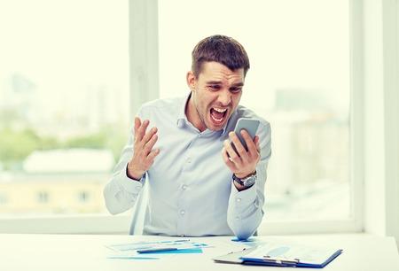 loco: negocio, la gente, el estrés y la tecnología concepto - cerca de negocios enojado gritando con teléfono inteligente